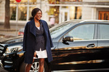 Success stylish african american woman in coat against black business suv car. - 233227880