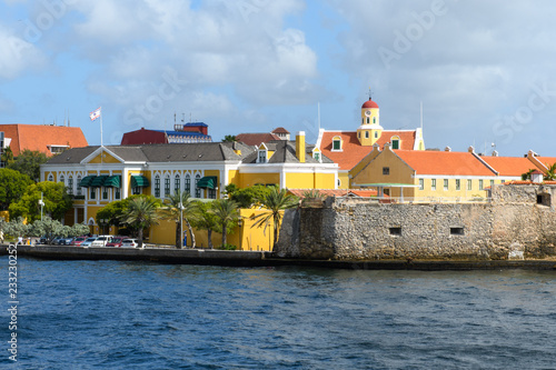 View from the sea to the embankment of the city with yellow houses under the red roof, palm trees and a stone wall of the ancient fortress