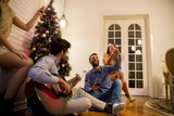 Happy people celebrating Christmas and New Year by fir-tree at home and playing guitar - 233231484