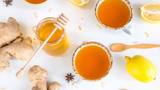 Tea with turmeric among products for improving immunity and treating colds - ginger, lemon and a jar of honey with a wooden spoon - 233237491