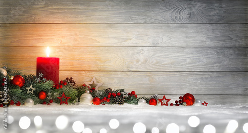 Hintergrund für Weihnachten oder Advent mit Holz, Kerze, Lichtern und Dekoration auf Schnee - 233242637