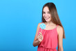 Young girl with lollipop on blue background