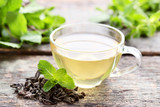 Cup of tea with mint leafs on grey wooden table - 233252223