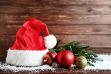 Santa claus hat with baubles and fir tree branches on wooden table