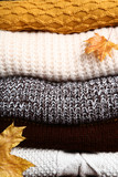 Background of folded sweaters with autumn leafs - 233253444