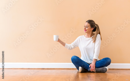 453c4bedf17 Young woman drinking a cup of coffee against a big interior wall ...