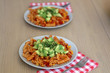 Two plates of pasta with tomato sauce, peppers, corn, avocado and herbs. Selective focus. - 233280827