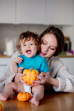 Happy white mother and son with pumpkin. Domestic image at kitchen - 233281092