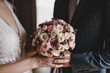 Beautiful bride's bouquet with different flowers. Hands of newlyweds.