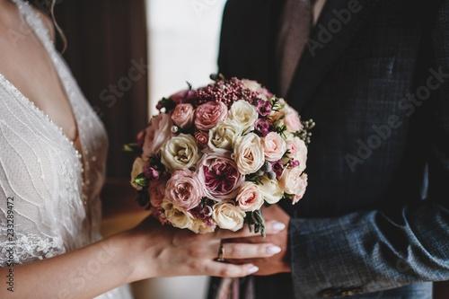 fototapeta na ścianę Beautiful bride's bouquet with different flowers. Hands of newlyweds.