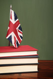 Books and UK flag in front of a green chalkboard - 233294869