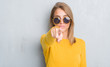 Leinwandbild Motiv Beautiful young woman standing over grunge grey wall wearing retro sunglasses pointing with finger to the camera and to you, hand sign, positive and confident gesture from the front