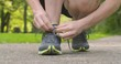 Female runner tying a loose shoe lace in a park.