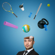 A view of a handsome young man's head cracked open with various sports equipment popping out isolated on blue background.