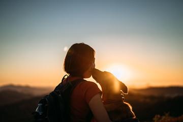 dog kissing girl at sunset