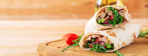 Tortillas wraps with chicken and vegetables on  wooden background. Chicken burrito. Banner. Healthy food. © timolina