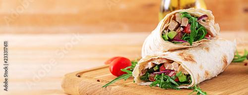 Leinwandbild Motiv Tortillas wraps with chicken and vegetables on  wooden background. Chicken burrito. Banner. Healthy food.