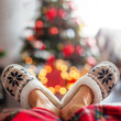 Leinwandbild Motiv Legs in slippers on Christmas tree background