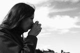 Woman is drinking tea on the waterfront. Young brunette on a journey. Bw. - 233329261