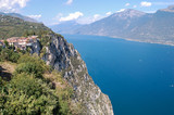 Mountains and a lake,/ Panoramic view from a great height on the lake surrounding Lake Garda. On the cliffs you can see a mountain road and tunnels. - 233332287