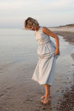 Woman in dress walks barefoot in the water by the sea  - 233341463