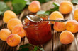 Leinwanddruck Bild - Glass Jar of Apricot jam on wooden table with ripe apricots at background