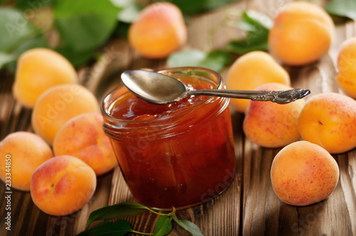Leinwanddruck Bild Glass Jar of Apricot jam on wooden table with ripe apricots at background