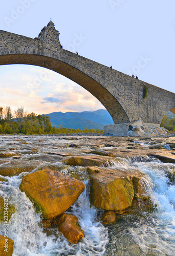 mata magnetyczna detail of the old Roman bridge with stone arch and river flowing in the middle of the rocks in the medieval village Bobbio on the hills near Piacenza, Italy