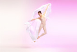 Young graceful female ballet dancer or classic ballerina dancing at pink studio. Caucasian model on pointe shoes - 233347424