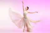 Young graceful female ballet dancer or classic ballerina dancing at pink studio. Caucasian model on pointe shoes - 233347479