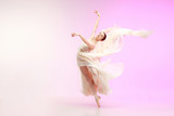 Young graceful female ballet dancer or classic ballerina dancing at pink studio. Caucasian model on pointe shoes - 233347605