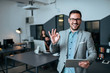Handsome young businessman showing OK gesture in modern office. Colleagues in the background.