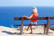woman sitting on bench on seashore. Vacation and relaxation concept.