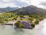Ancient Marae Taputapuatea temple complex on the lagoon shore with mountains on background. Raiatea island. French Polynesia, Oceania. - 233351477