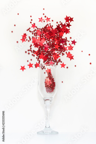Red confetti in shape of stars poured out glasses of champagne. Top view. Christmas party. Magic night. - 233355646