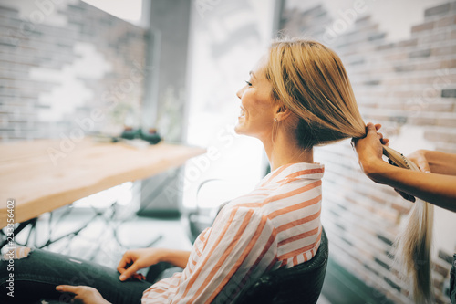 Portrait of beautiful young woman getting haircut