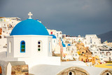 Traditional and famous houses and churches with blue domes in Oia, Santorini, Greece - 233358466