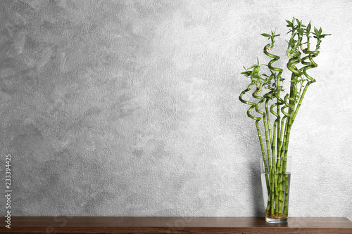 Table with bamboo plant in glass vase near color wall. Space for text