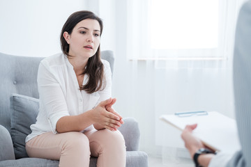 Worried woman with problem talking to psychotherapist during therapy in the office © Photographee.eu