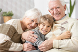 Loving grandparents cuddling on a couch with teenage grandson - 233395078