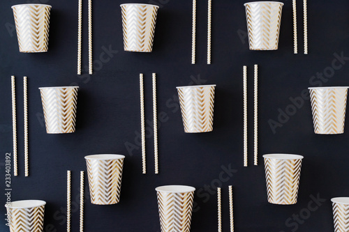 Foto Murales Party decoration background. Golden disposable dishes on dark wooden background