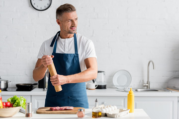 Smiling man enjoying cooking dinner in kitchen