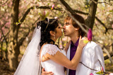Newlyweds on nature background with blossoming magnolias - 233407266