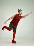 The happy smiling friendly man dressed like a funny gnome or elf running on an isolated gray studio background. The winter, holiday, christmas concept - 233409457