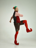 The happy smiling friendly man dressed like a funny gnome or elf posing on an isolated gray studio background. The winter, holiday, christmas concept - 233409872