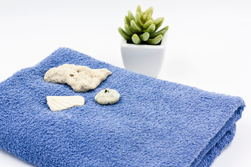 detail of set of two bath towels with dried flowers and sea stones in blue and white color