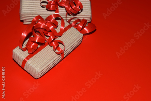 xmas background with copy space, top view of gift box wrapped in cardboard packaging with red ribbon on red surface