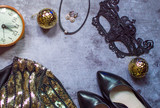 Accessories for accessories the New Year and New Year holiday 2019: carnival mask with an alarm clock, checker and gold dress made of sequins. On the clock time charges at the party 23:55. Flat lay