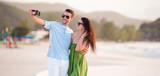 Happy couple taking a selfie photo on white beach. - 233424005