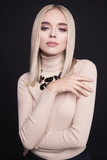 Beautiful young blonde with classic makeup and modern jewelry
